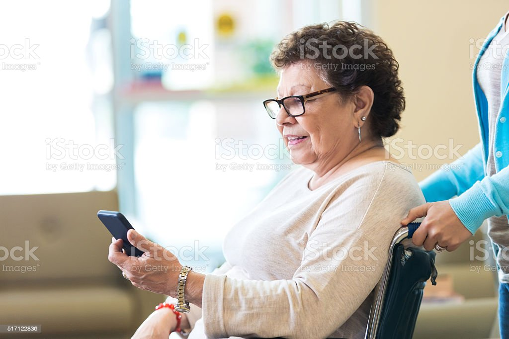 Senior woman using smart phone in nursing home stock photo
