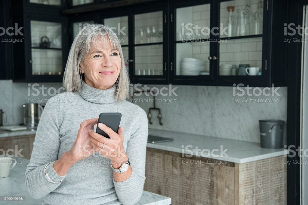 Senior woman using smartphone in modern kitchen stock photo