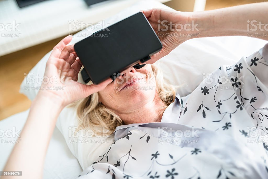 senior woman using the VR simulator on the bed stock photo