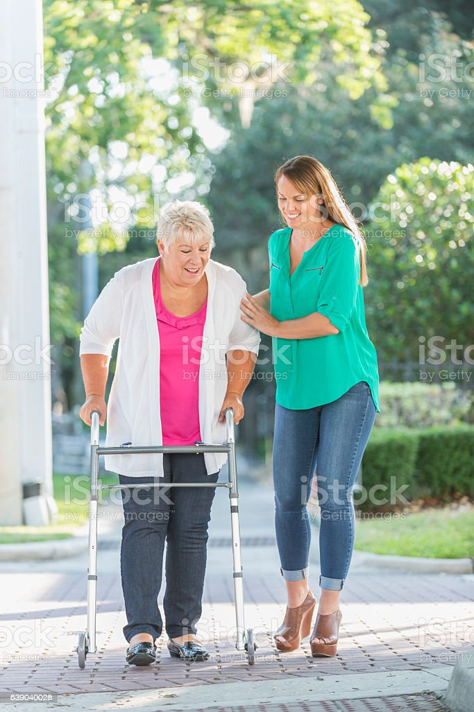 Senior woman using walker, helped by adult daughter stock photo