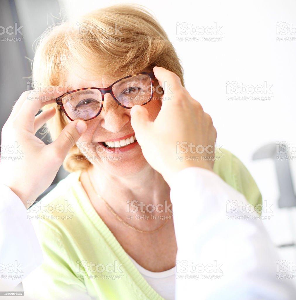 Senior woman visiting optician. stock photo