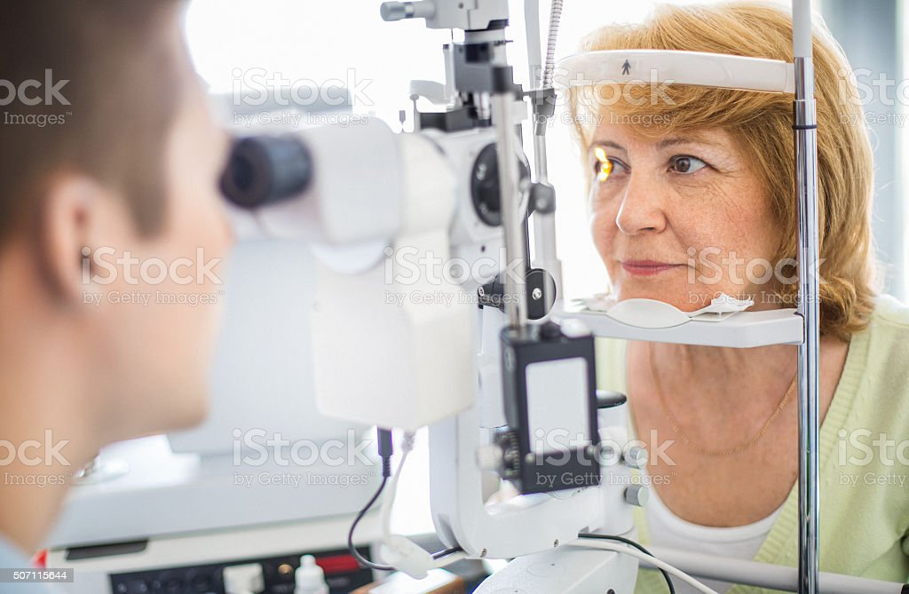 Senior woman visiting optician. stock photo