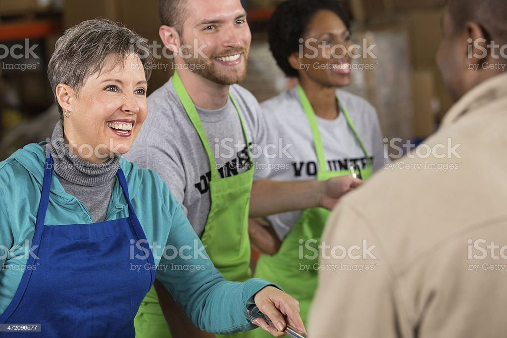 Senior woman volunteering at food bank soup kitchen stock photo