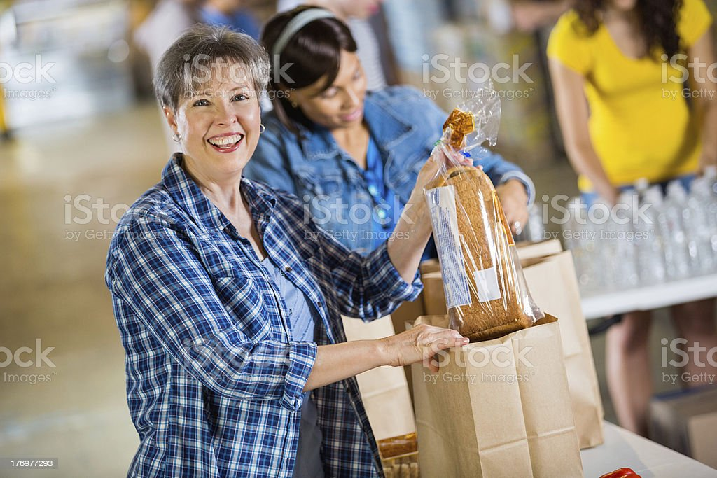 Senior woman volunteering to sort food donations royalty-free stock photo