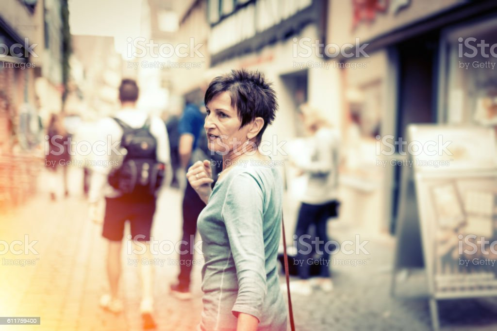 Senior woman walking through the streets of Tübingen, Germany stock photo