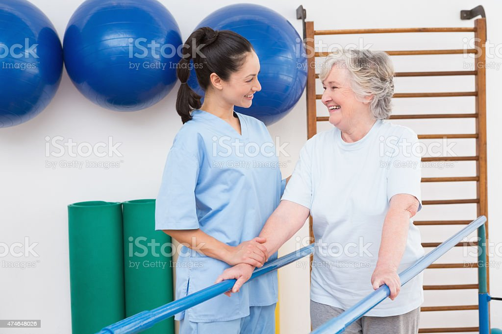 Senior woman walking using parallel bars with therapist stock photo