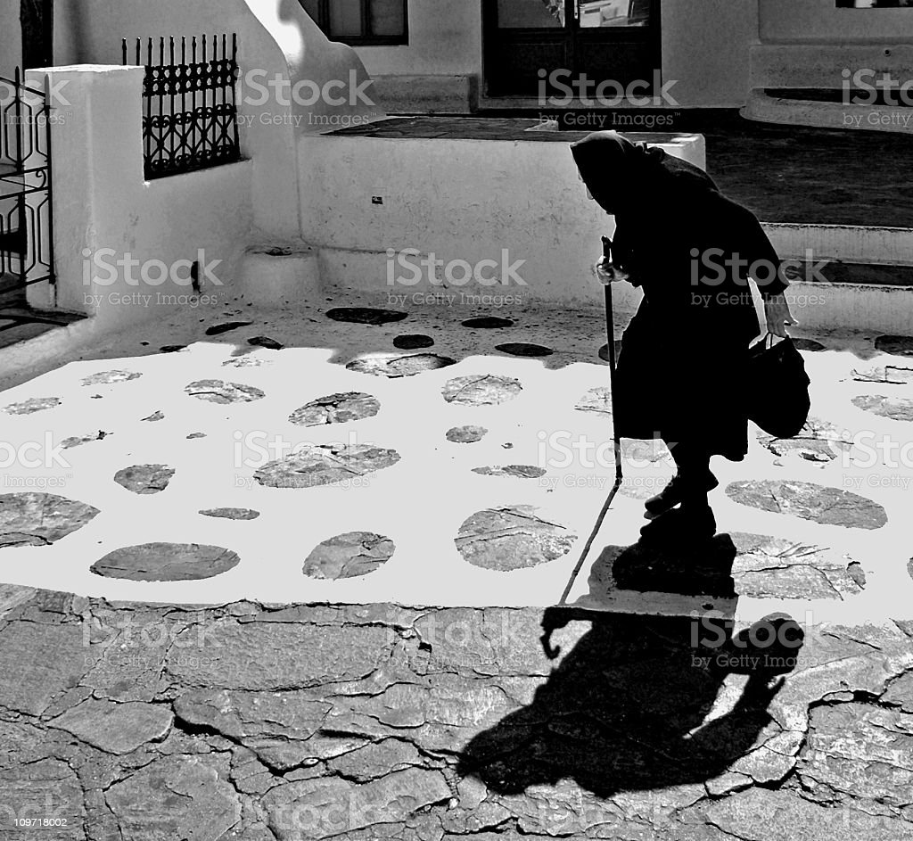 Senior Woman Walking With Cane in Town, Black and White stock photo