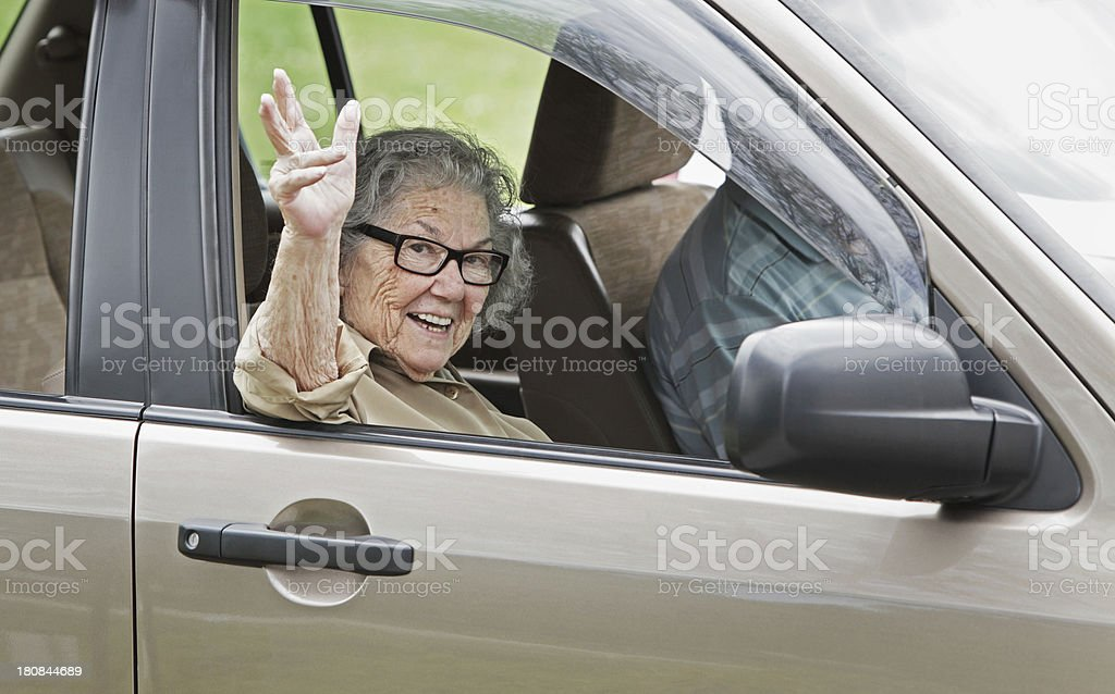 Senior Woman Waving From Car Window royalty-free stock photo