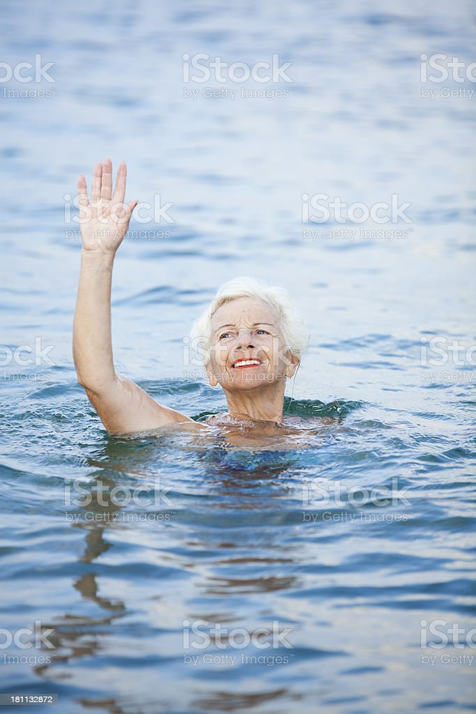 Senior woman waving in the sea royalty-free stock photo