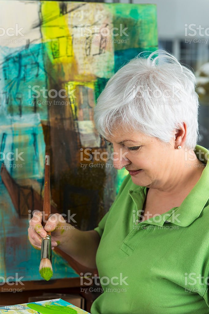 Senior woman wearing a green t-shirt painting in an art studio stock photo