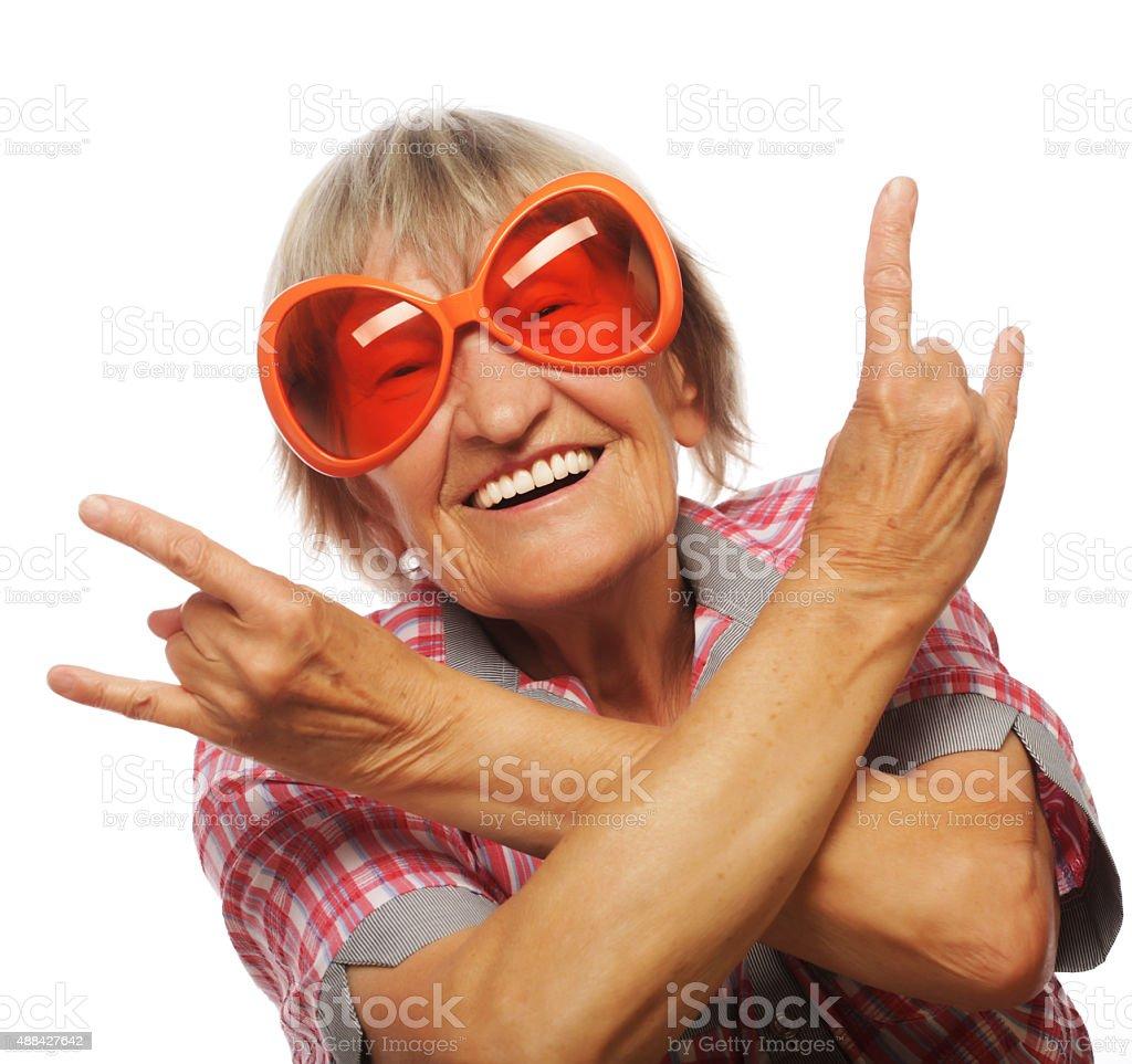 Senior woman wearing big sunglasses doing funky action stock photo