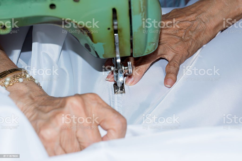 Senior woman with a sewing machine stock photo