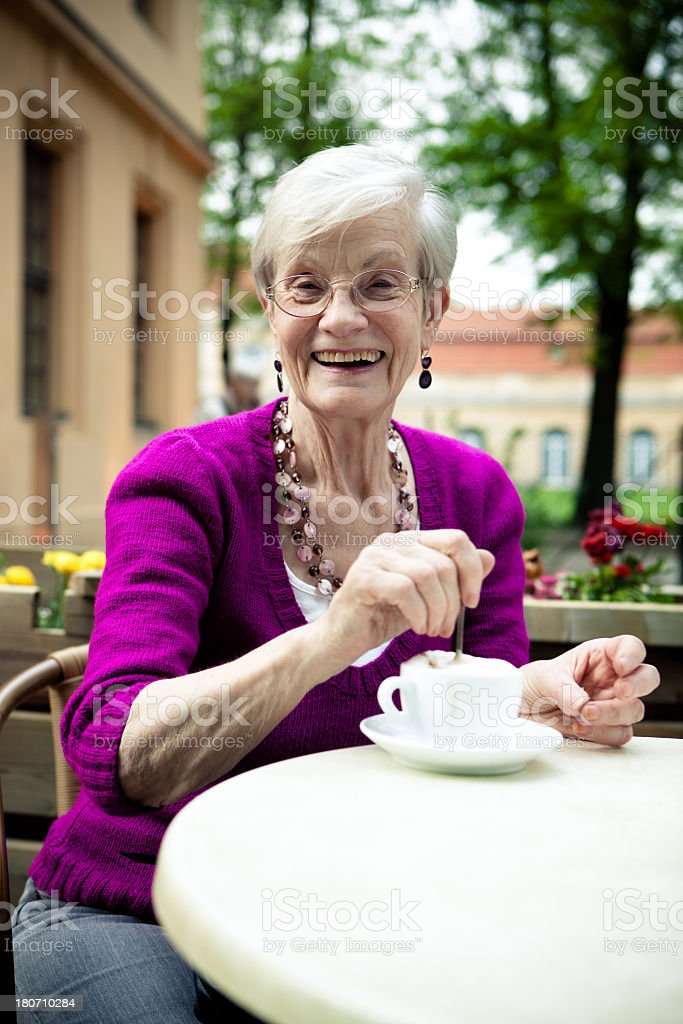 Senior woman with a Toothy Smile in sidewalk cafe royalty-free stock photo
