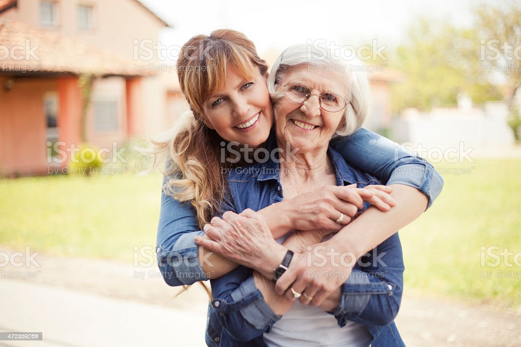 Senior woman with adult daughter hugging her from behind stock photo