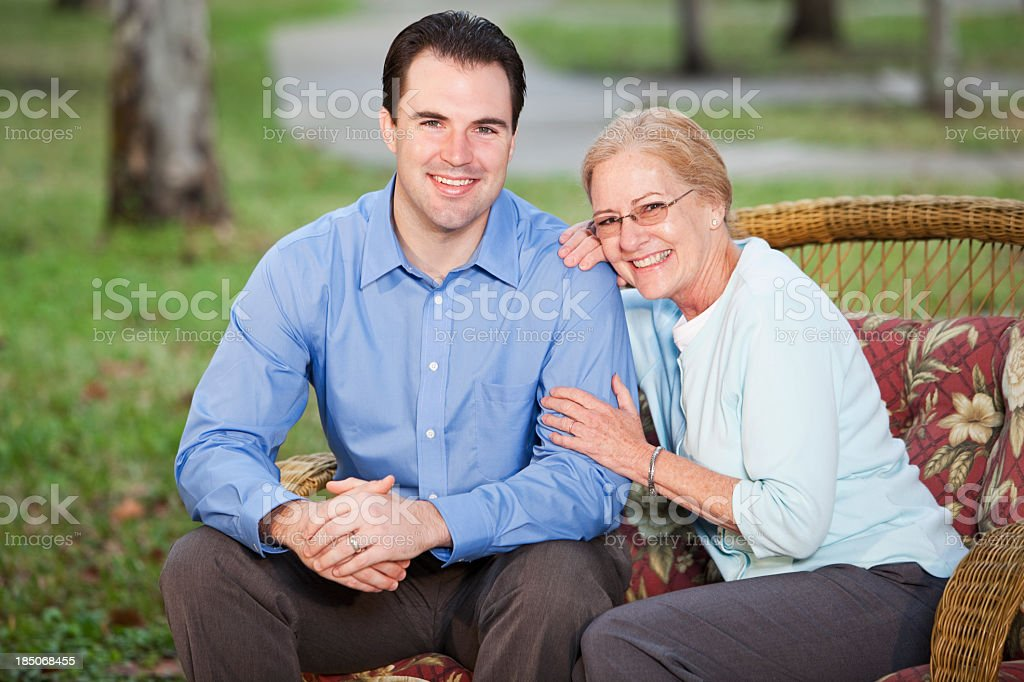 Senior woman with adult son on patio stock photo