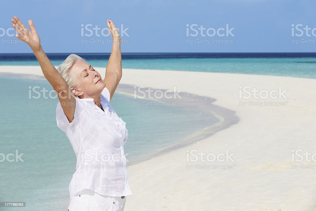 Senior Woman With Arms Outstretched On Beautiful Beach royalty-free stock photo