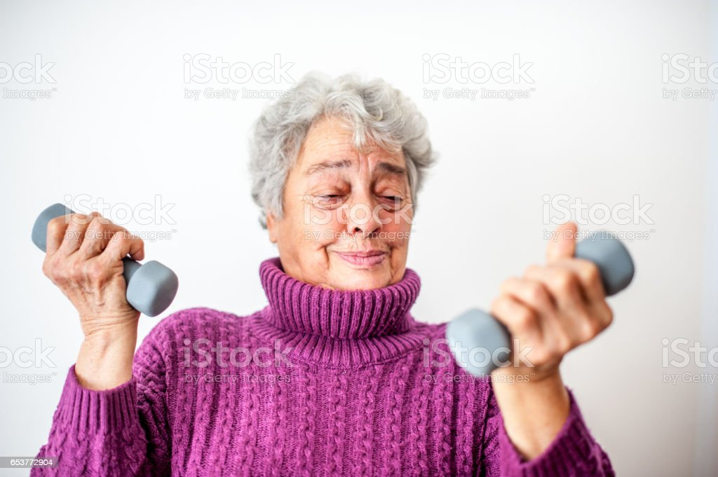 Senior Woman With Arthritic Hands Lifting Weights - Portrait stock photo