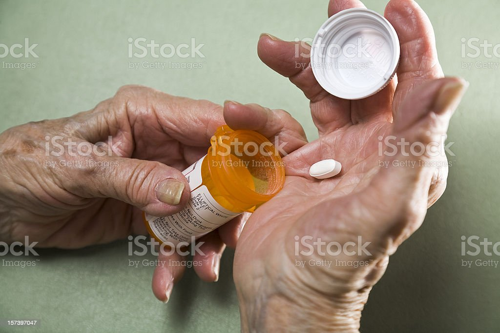 senior woman with arthritis holding prescription medicine pill bottle royalty-free stock photo