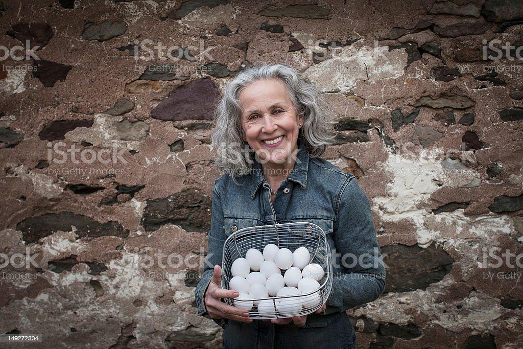 Senior woman with basket of eggs stock photo