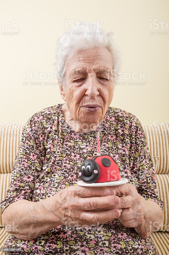 senior woman with birthday cake stock photo