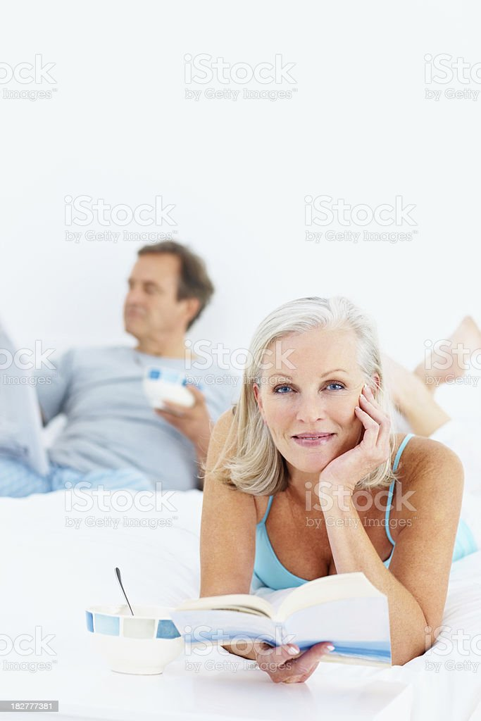 Senior woman with book in bed and man at back royalty-free stock photo