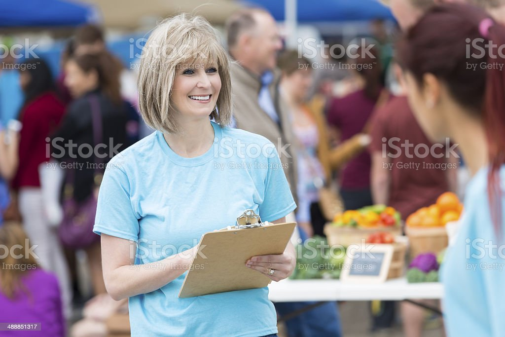 Senior woman with clipboard volunteering at outdoor farmer's market booth stock photo