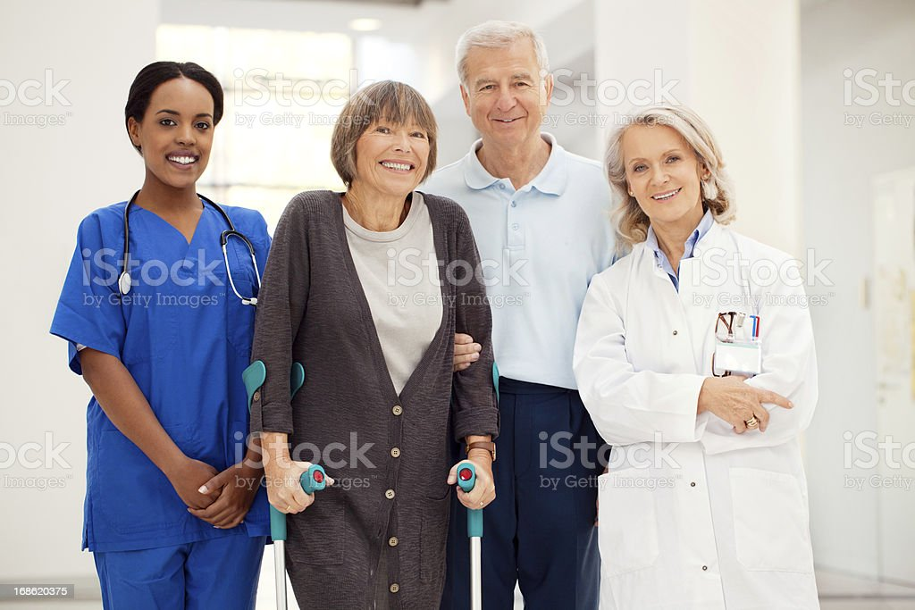 Senior woman with crutches and hospital staff stock photo