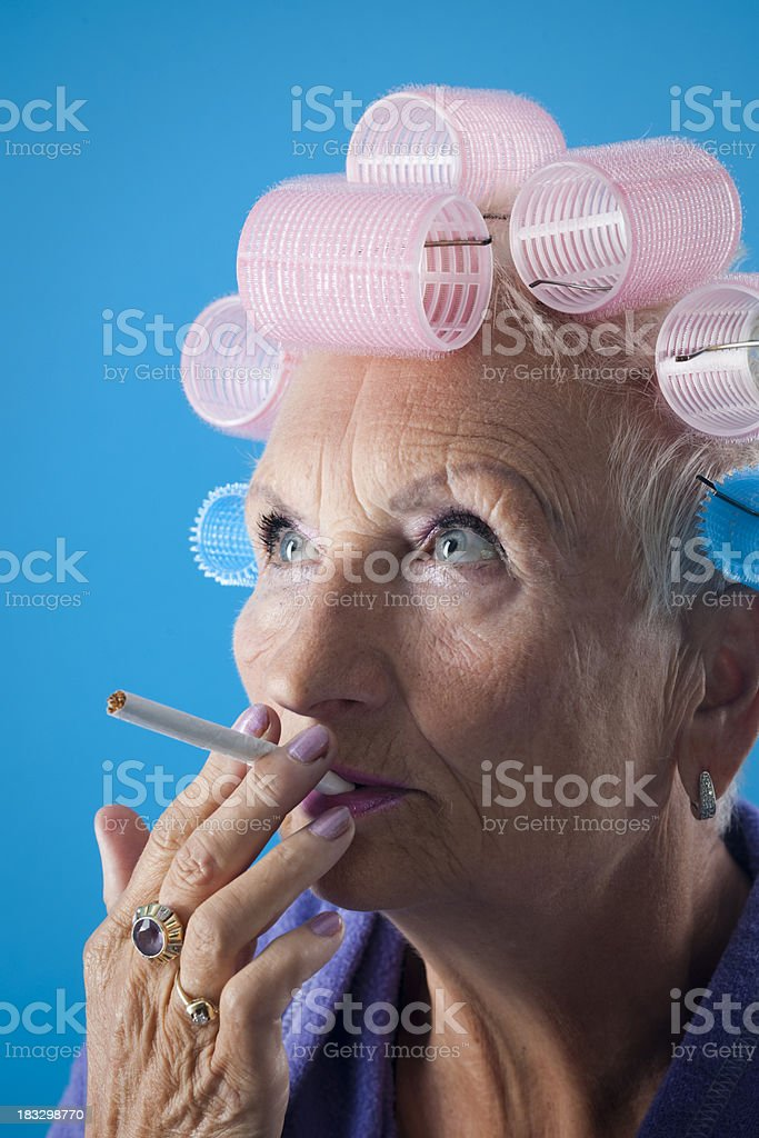 Senior woman with curlers is smoking royalty-free stock photo