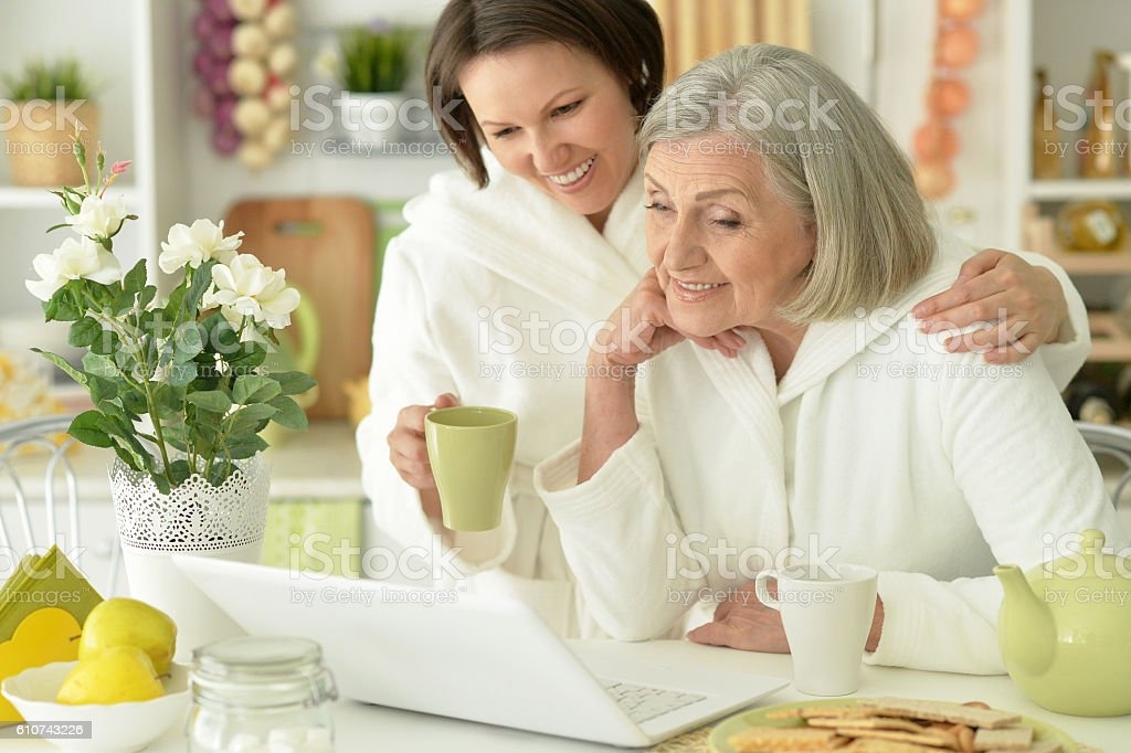 Senior woman with daughter  with laptop stock photo