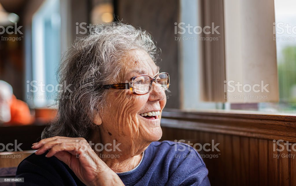 Senior Woman With Dementia Looking Out Restaurant Window stock photo