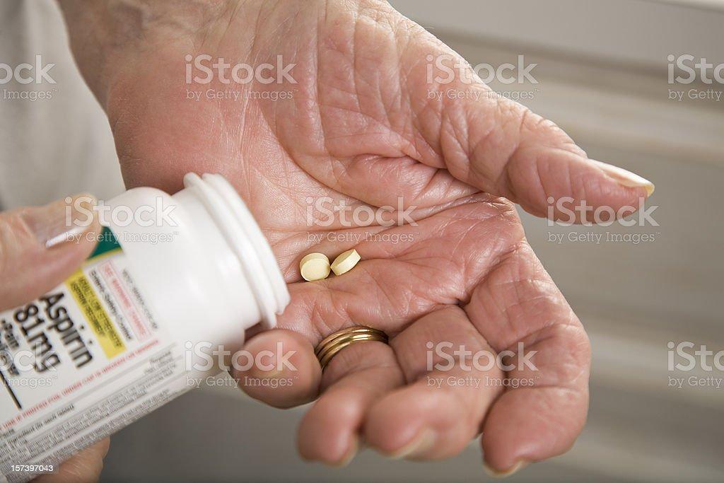 senior woman with distorted arthritis hand taking aspirin pills stock photo