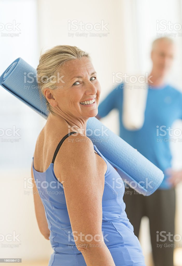 Senior Woman With Exercise Mat At Home royalty-free stock photo