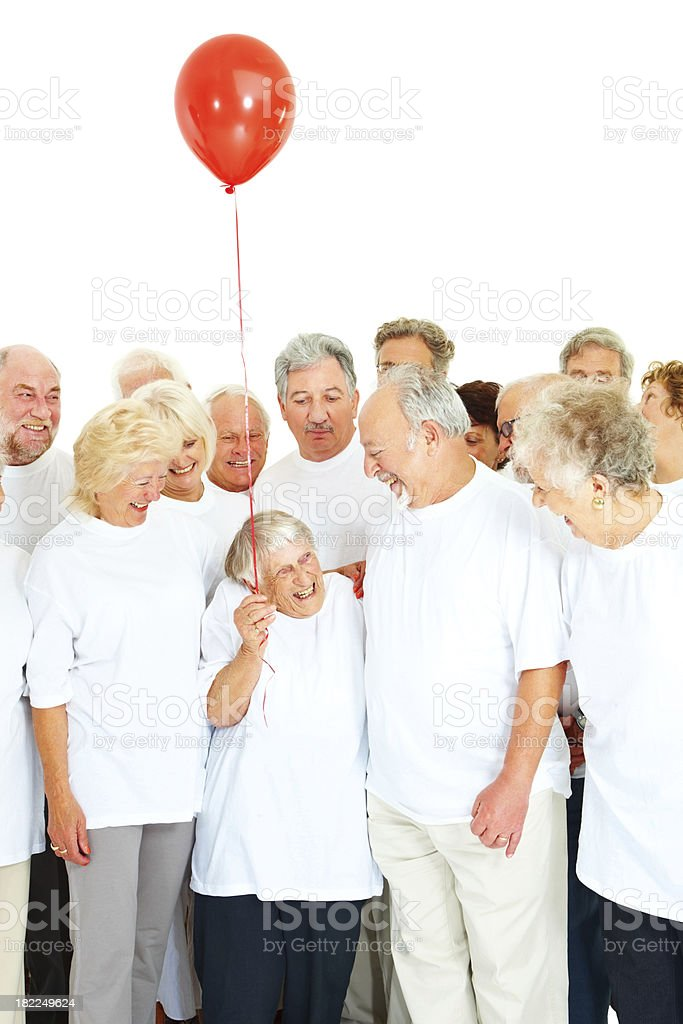 Senior woman with friends holding a red balloon royalty-free stock photo
