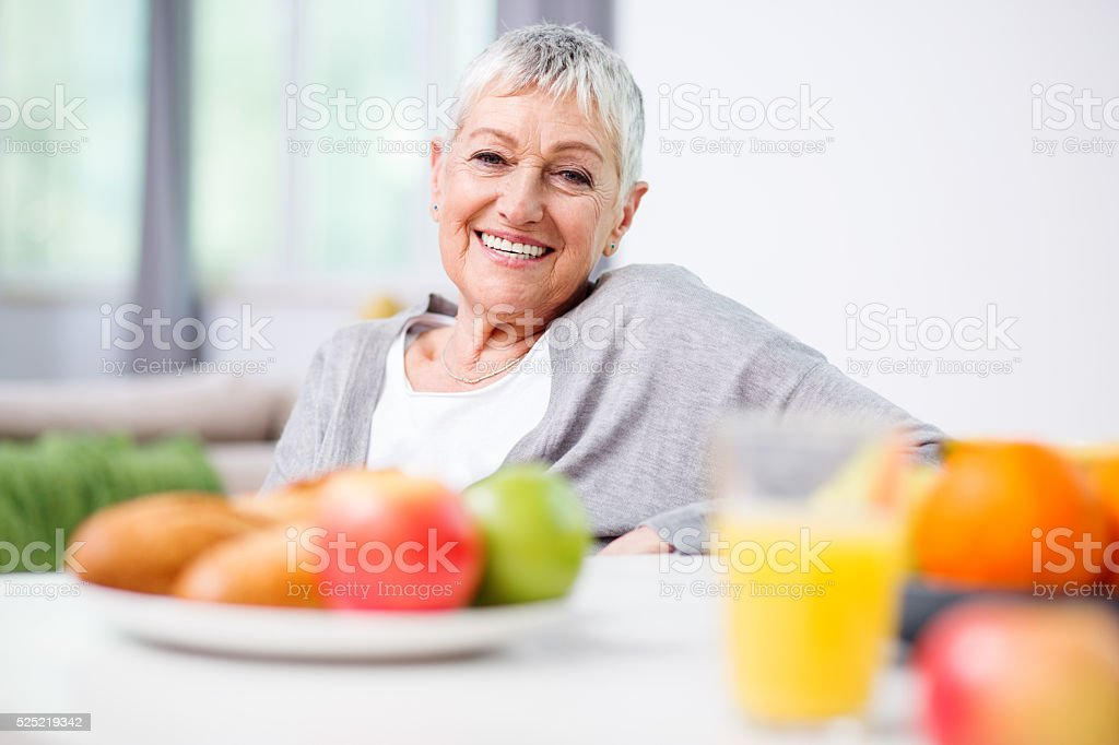 Senior woman with fruits and orange juice stock photo