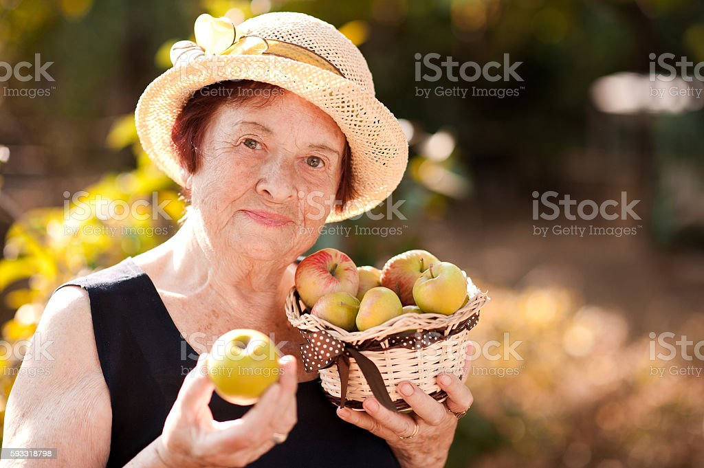 Senior woman with green apples outdoors stock photo