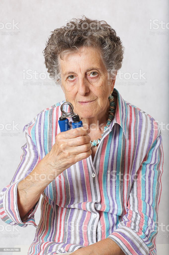 Senior woman with hand expander stock photo