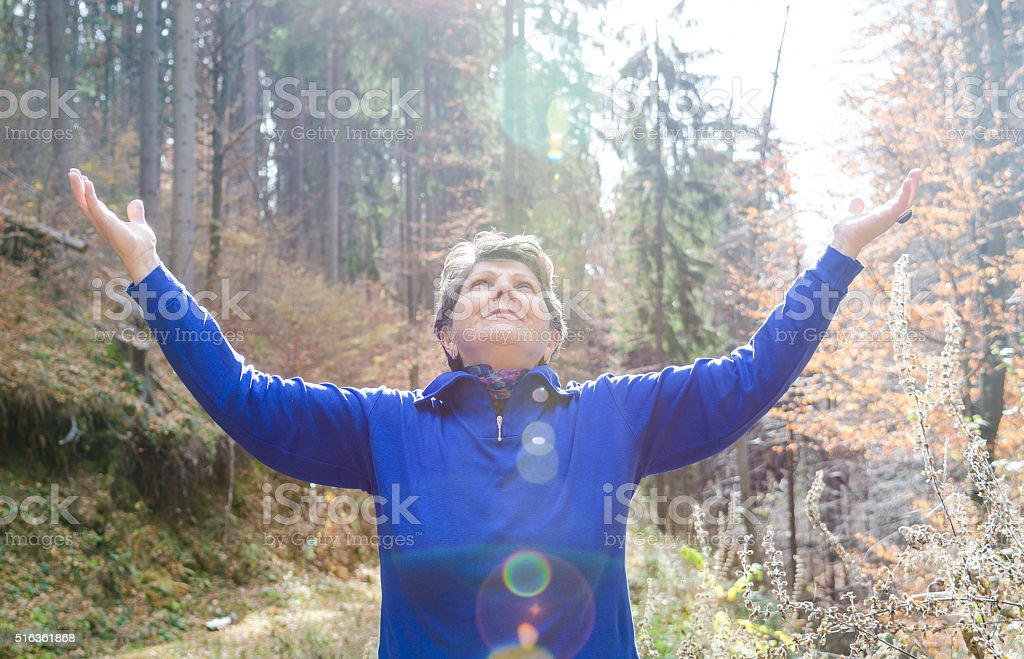 Senior Woman with Hands Uplifted stock photo