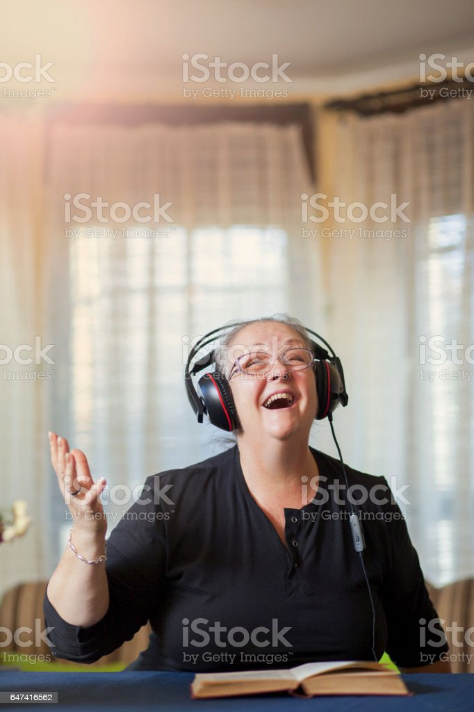 Senior woman with headphones singing and enjoying in song stock photo