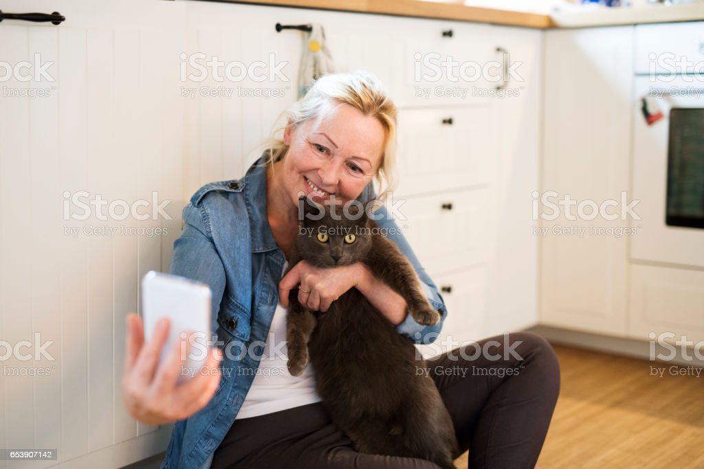 Senior woman with her cat at home taking selfie. stock photo