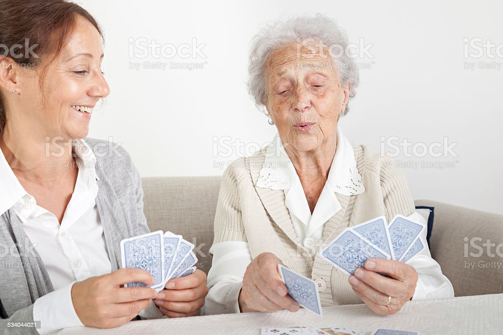 Senior woman with her home caregiver playing cards stock photo