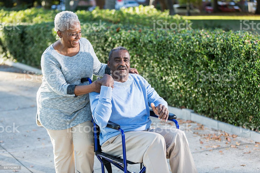 Senior woman with her husband in a wheelchair stock photo