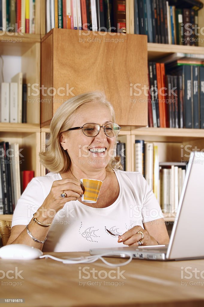 Senior woman with laptop and books shelves on the background royalty-free stock photo