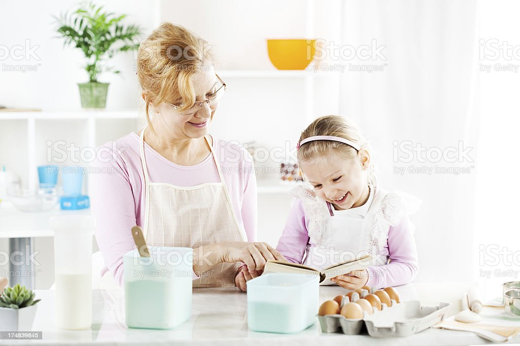 Senior woman with little girl in the kitchen. royalty-free stock photo
