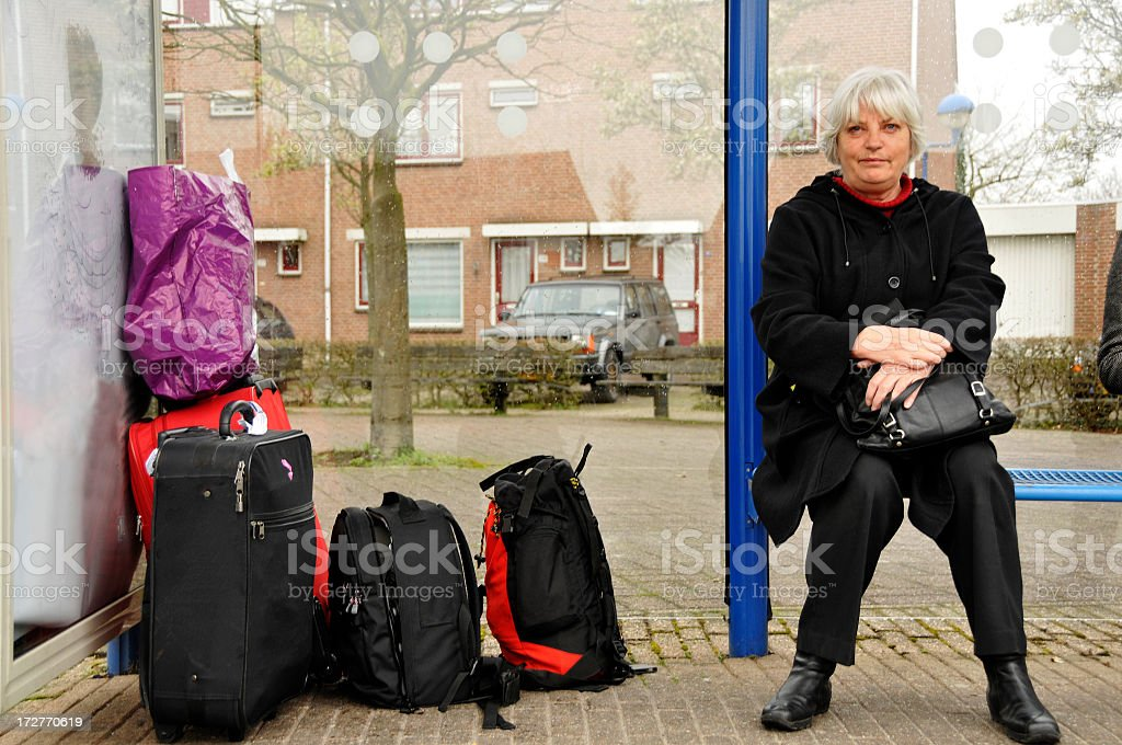 Senior woman with luggage in busshelter royalty-free stock photo