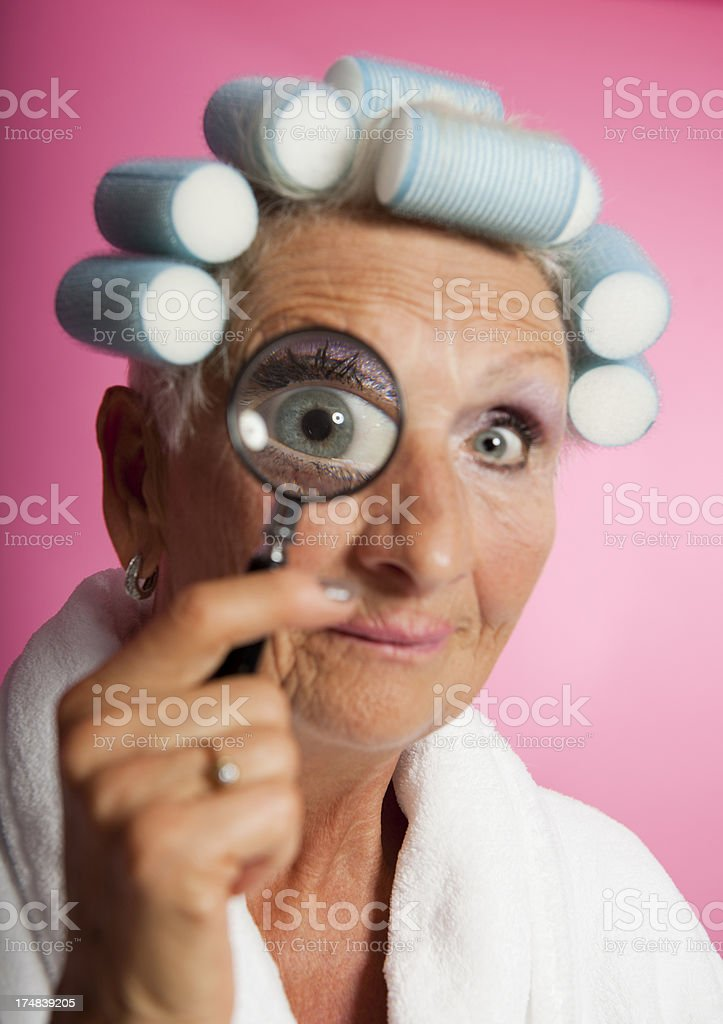 Senior woman with magnifying glass royalty-free stock photo
