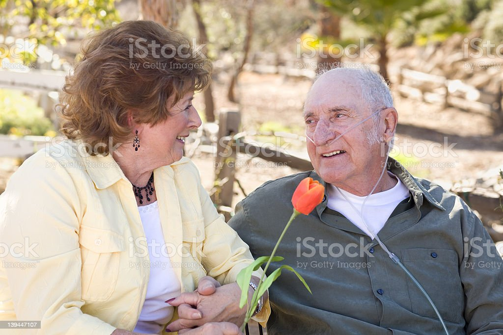 Senior Woman with Man Wearing Oxygen Tubes stock photo