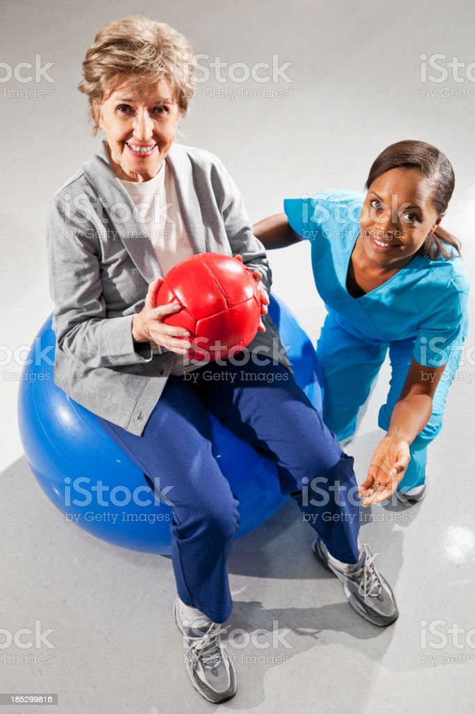 Senior woman with physical therapist using fitness balls stock photo