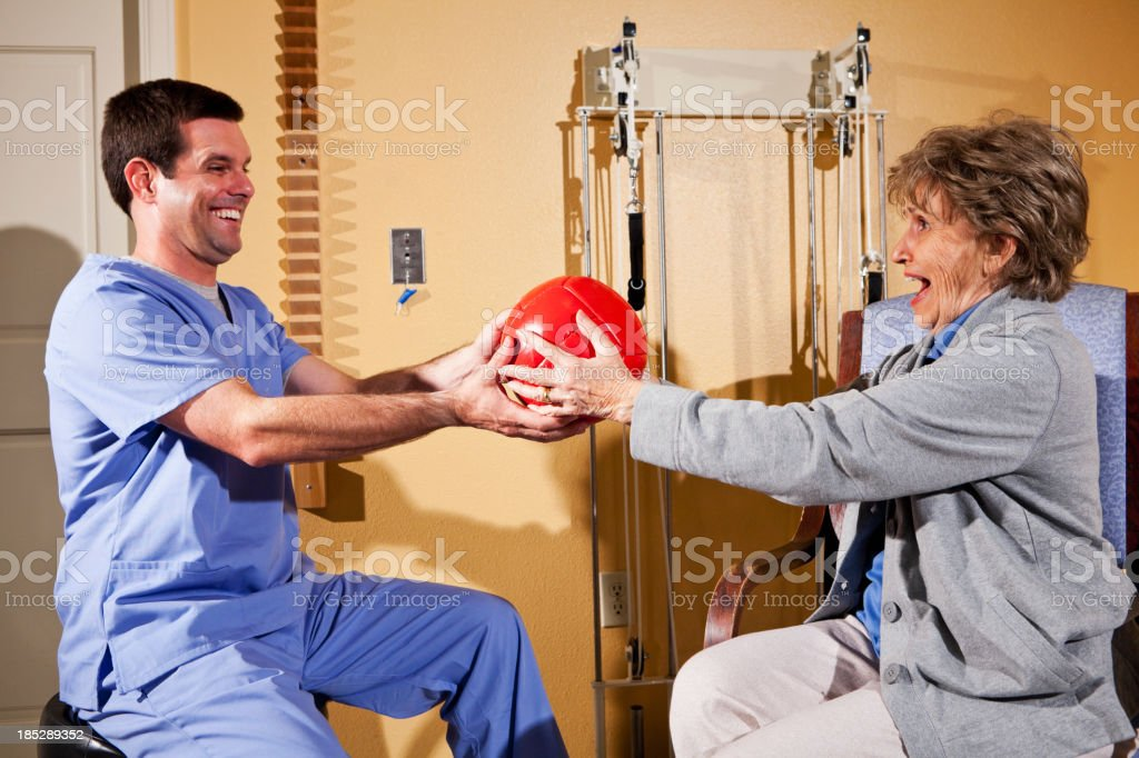 Senior woman with physical therapist using medicine ball stock photo