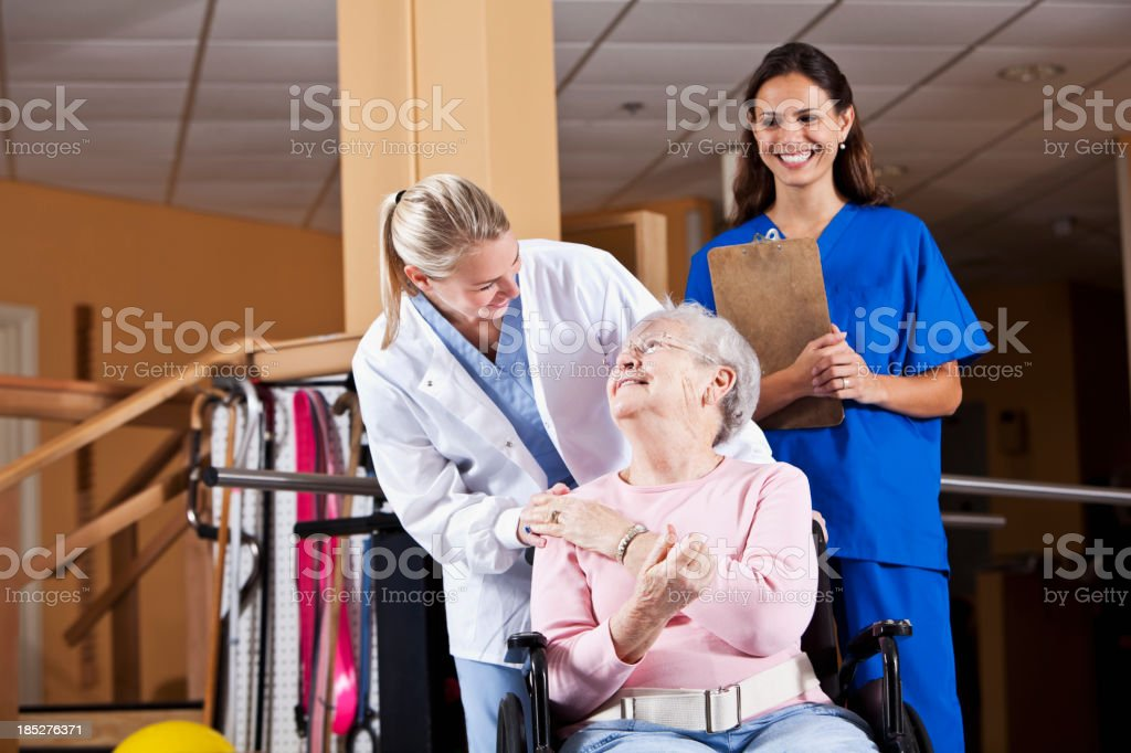 Senior woman with physical therapists stock photo