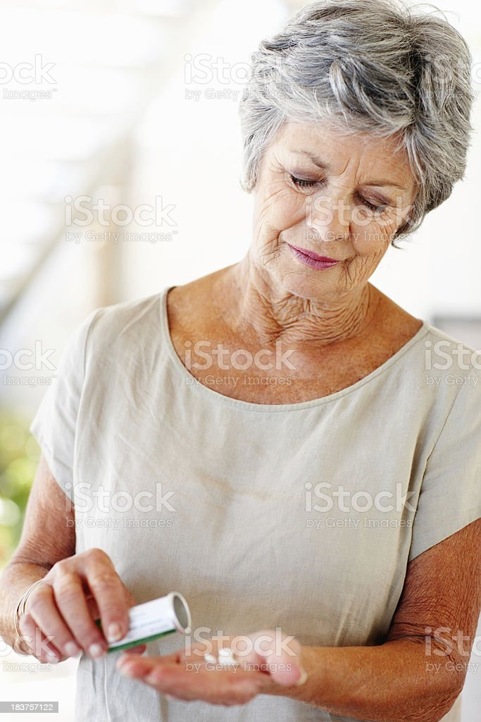Senior woman with pills in her hand royalty-free stock photo